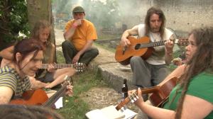 Festivalbesucher sitzen entspannt zusammen und machen Musik
