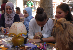 Junge Frauen bemalen Hände mit Henna-Ornamenten
